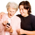 elderly woman using smartphone and her adult daughter